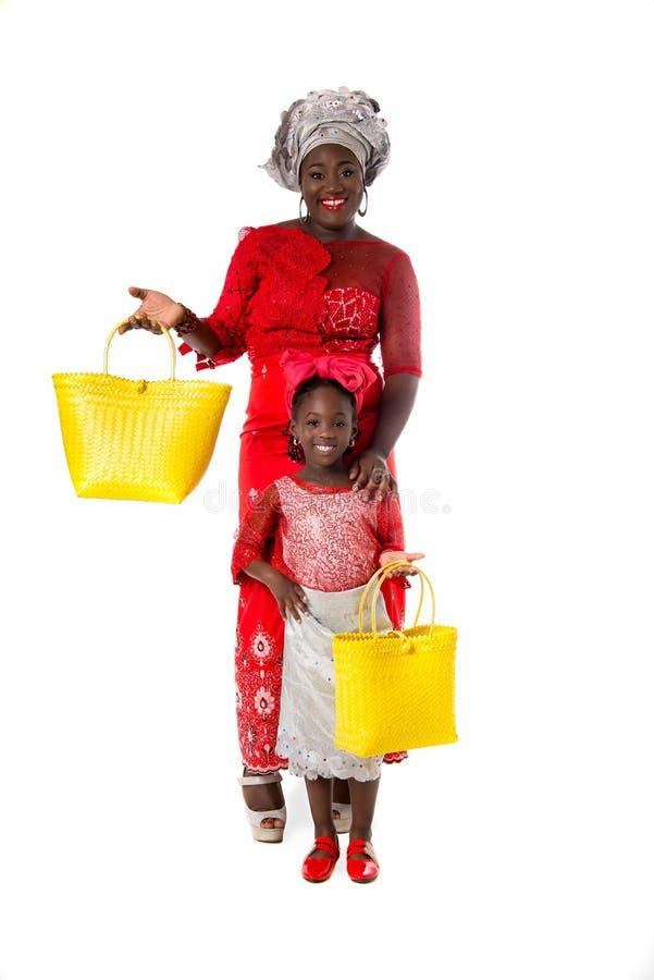 Afrikanerin mit kleinem Mädchen in der traditionellen Kleidung mit Einkaufstaschen Getrennt stockbild