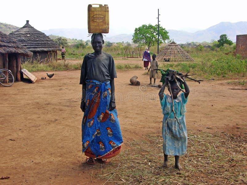Afrikanerin- u. Kinderdorfbewohner, die tägliches Arbeits- u. Aufgabendorfleben tun lizenzfreie stockbilder