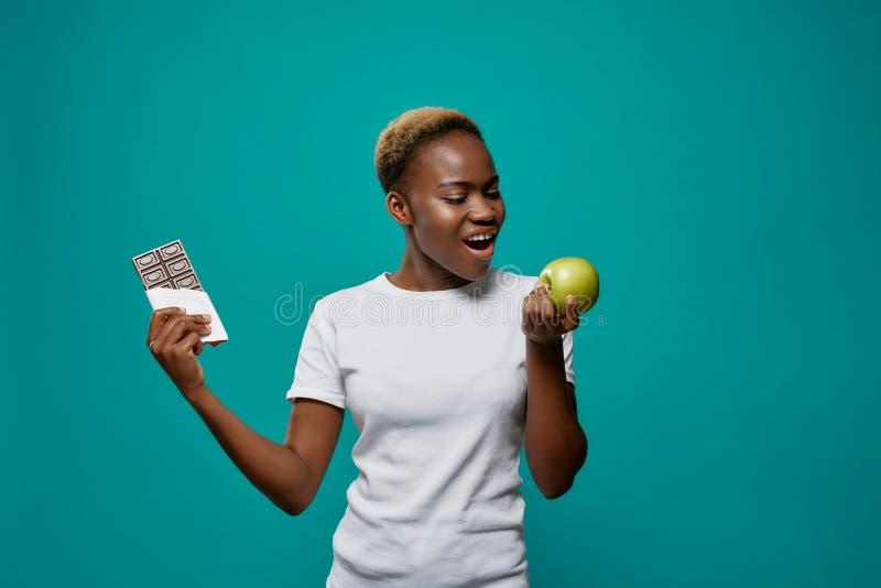 Afrikanerinholdingapfel und dunkler Schokoriegel lizenzfreies stockfoto