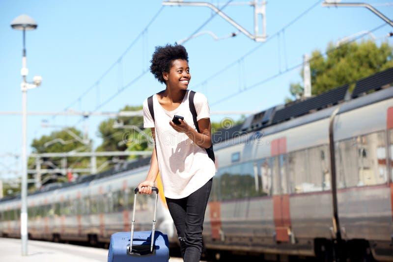 Afrikanerinreisender, der mit Mobiltelefon und auf Bahnplattform steht lizenzfreies stockbild