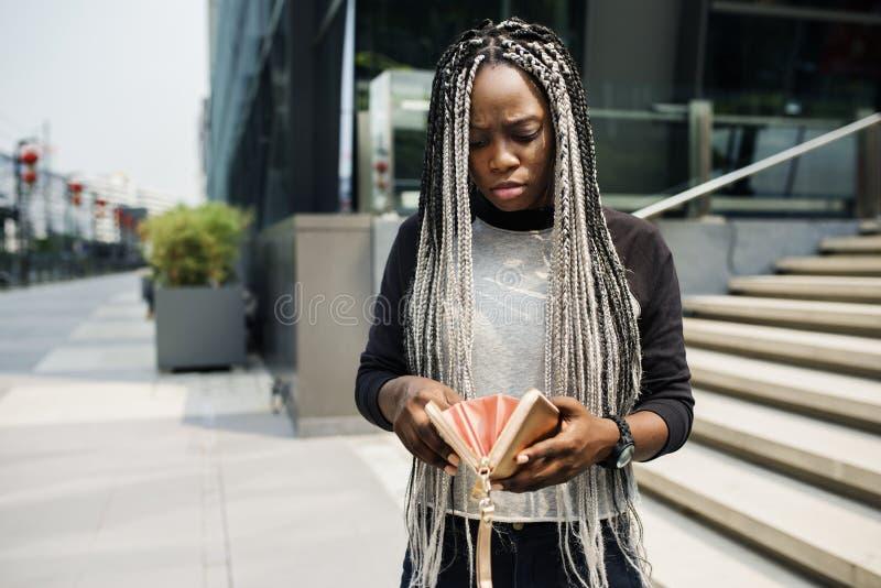 Afrikanische Abstammung, die ihre Geldbörse überprüft lizenzfreies stockbild