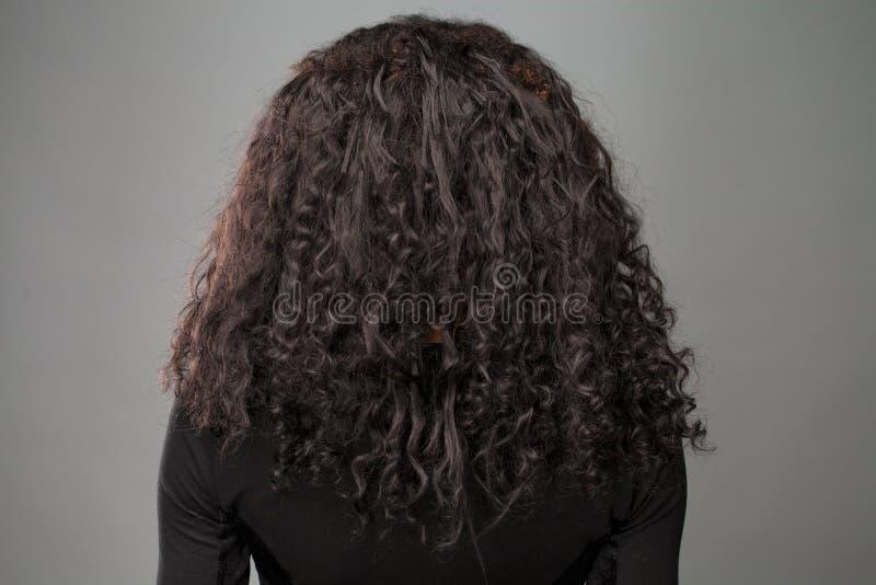 Afrikanische brunette Frau, die ihr langes gelocktes Haar vorführt lizenzfreie stockfotografie