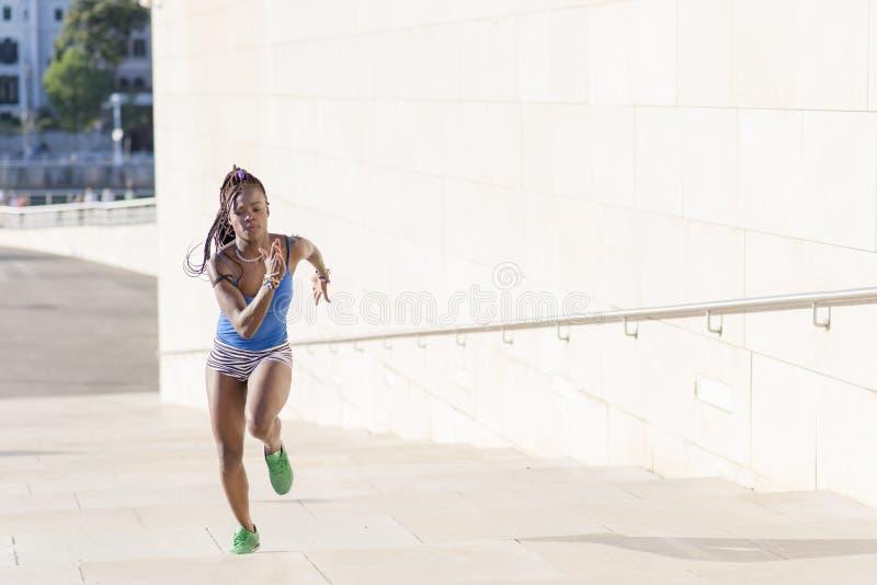 Afrikanische Frau des schönen Sports, die in die Straße, Gesundheitslebensstil c läuft lizenzfreie stockbilder