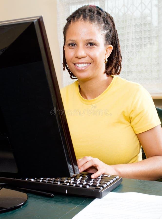 Afrikanische Frau, die Computer erlernt stockbilder