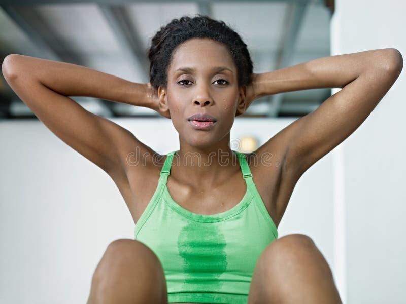 Afrikanische Frau, die Reihe des Knirschens in der Gymnastik tut lizenzfreies stockbild