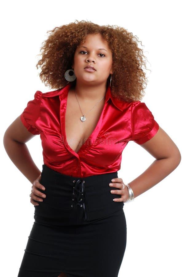 Afrikanische Frau, die rote Oberseite und schwarzes Kleid trägt stockbild
