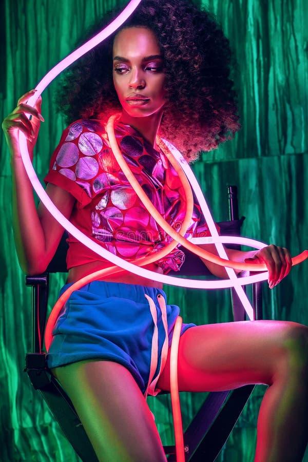 Afrikanische Frau mit rosa und rotem Neonlicht im Hintergrund lizenzfreies stockbild