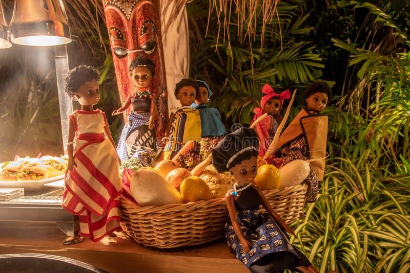 Afrikanische gekleidete Puppendekoration während des internationalen Kücheabendessens draußen gegründet am Inselrestaurant stockfoto