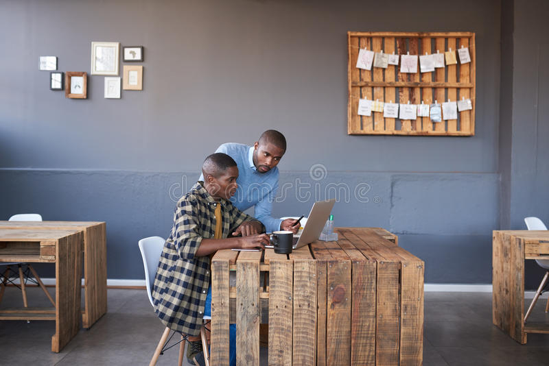 Afrikanische Geschäftsmänner, die zusammen an einem Laptop in einem Büro arbeiten stockfotos