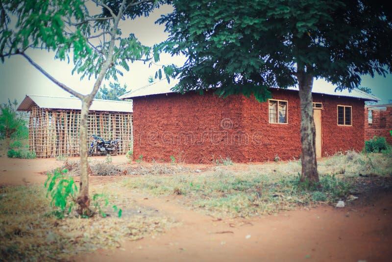 Afrikanische Häuser mit Bäumen außerdem lizenzfreie stockfotografie