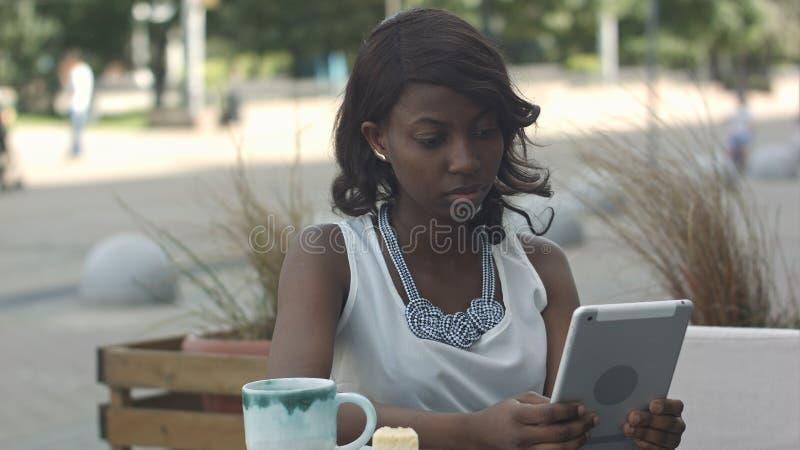 Afrikanische junge Geschäftsfraufunktion und mit Tablette Café im im Freien stockbilder