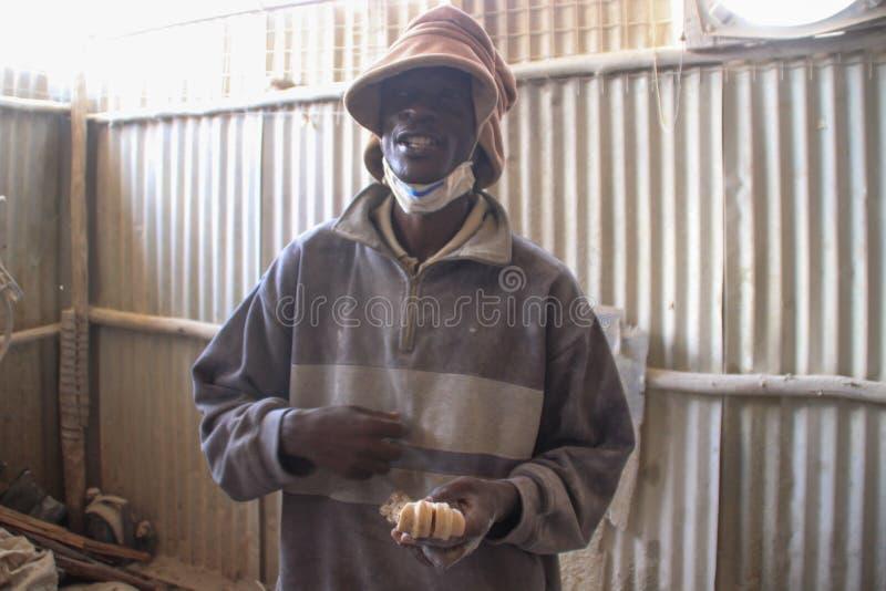 Afrikanische junge männliche Arbeitskraft an einer Andenkenfabrik in Nairobis schlechtestem Bezirk - Kibera lizenzfreie stockfotos