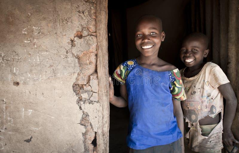 Afrikanische Kinder am Theingang zum Familienschlamm Hütte oder ` Banda-` lizenzfreie stockbilder