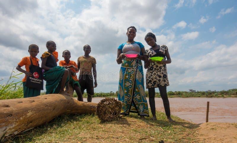 Afrikanische Landwirtfamilie, die das Mittagessen in Sabaki-Fluss isst stockfoto