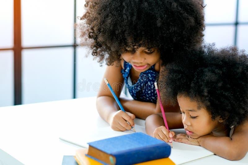 Afrikanische Mädchen als ältere und jüngere Schwester etwas auf Weißbuch nahe dem Buch vor Glasfenstern mit Tag schreiben oder ze stockfoto