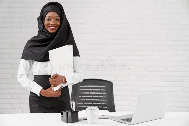 Afrikanische moslemische Frau, die bei Tisch, Ordner halten steht stockfotografie