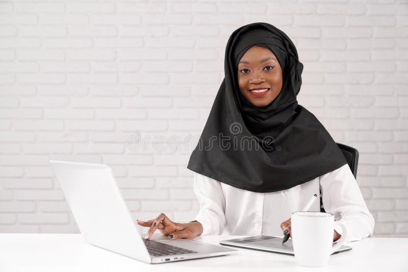 Afrikanische moslemische Geschäftsdame, die an Computer im Büro arbeitet lizenzfreie stockbilder
