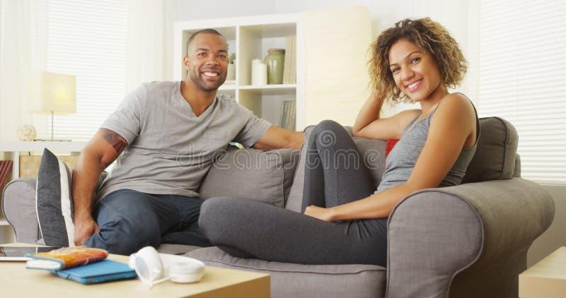 Afrikanische Paare, die auf dem Couchlächeln sitzen lizenzfreie stockbilder
