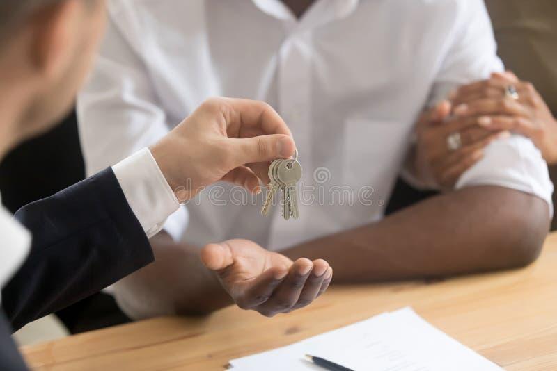 Afrikanische Paarinhaber kommen Schlüssel zum neuen Haus vom Grundstücksmakler stockbilder