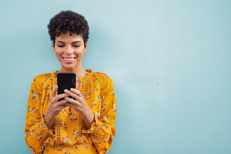Afrikanische stilvolle Frau, die intelligentes Telefon verwendet stockbild