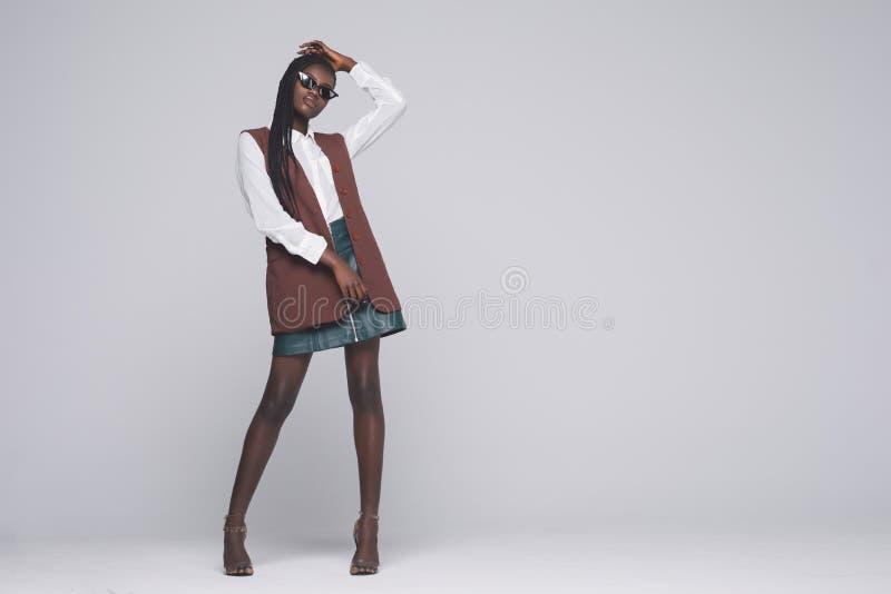Afrikanische vorbildliche Mädchenganzaufnahme der Mode lokalisiert auf grauem Hintergrund Stilvolle Frau der Schönheit, die Produ stockfoto