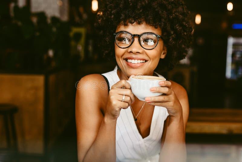 Afrikanische weibliche Entspannung am coffeeshop stockbild