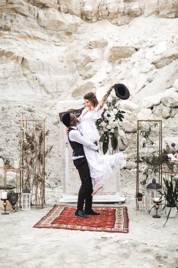 Afrikanischer Br?utigam und kaukasische Braut, die in einer boho Art vor dem Heiratsbogen von den frischen Blumen sich umfasst gr stockbilder