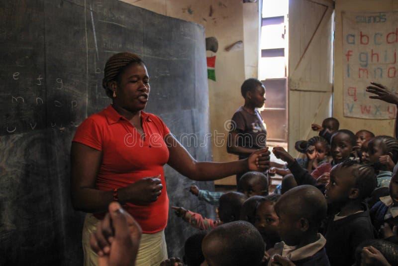 Afrikanischer freiwilliger Lehrer in der schlechtesten Schule in Kibera lizenzfreies stockbild