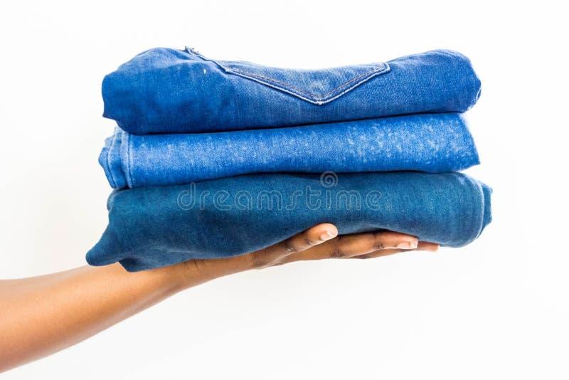 Afrikanischer Geschäftsfrau-Holdingstapel Kleidung, Jeans oder Denim in einer Hand stockfotos