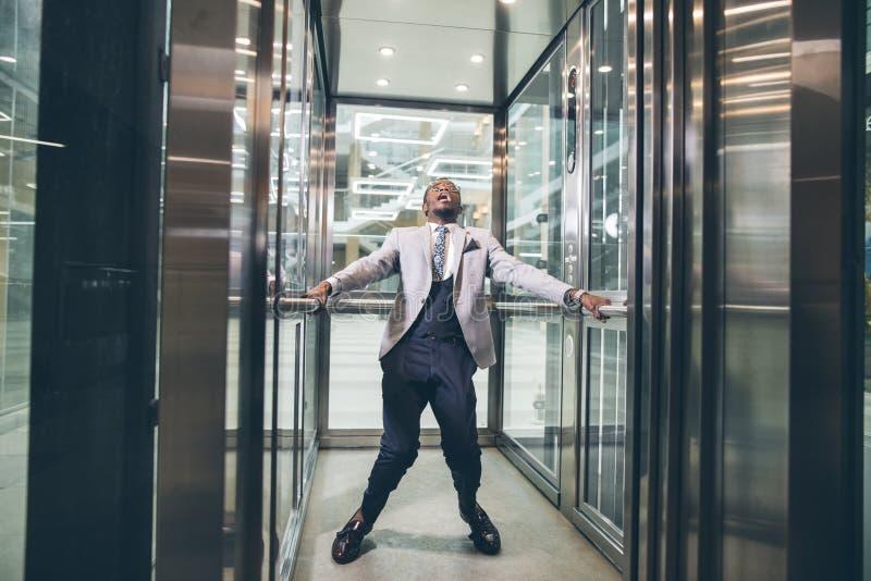 Afrikanischer Geschäftsmann, der im Aufzug schreit Furchtplatzangstkonzept stockfoto