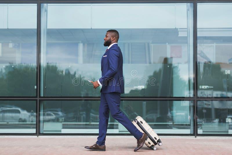 Afrikanischer Geschäftsmann, der mit dem Gepäck, kommend im Flughafen geht an stockfotos