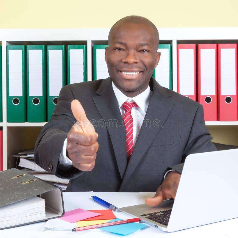 Afrikanischer Geschäftsmann, der sich Daumen in seinem Büro zeigt stockfotografie