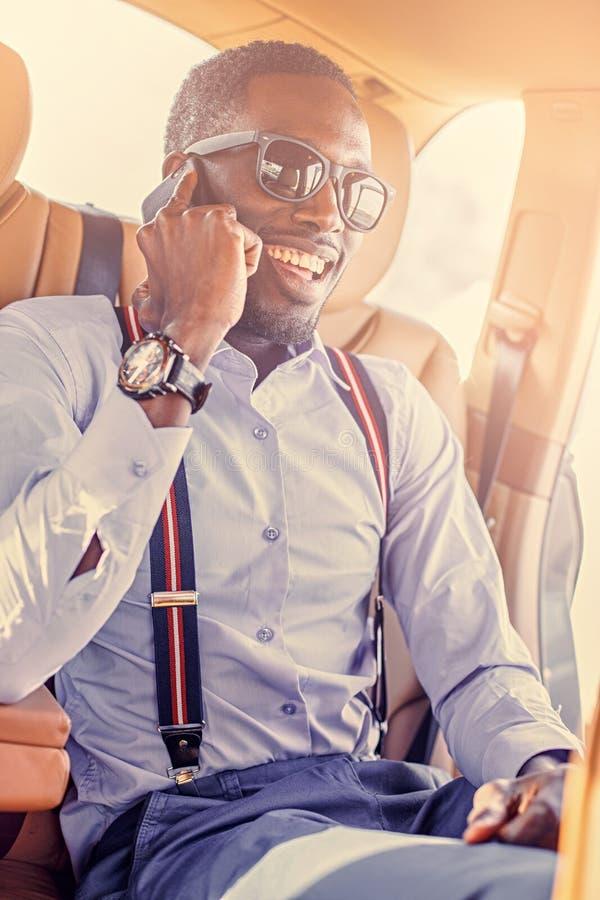 Afrikanischer Geschäftsmann im Auto, das über Smartphone spricht lizenzfreies stockbild