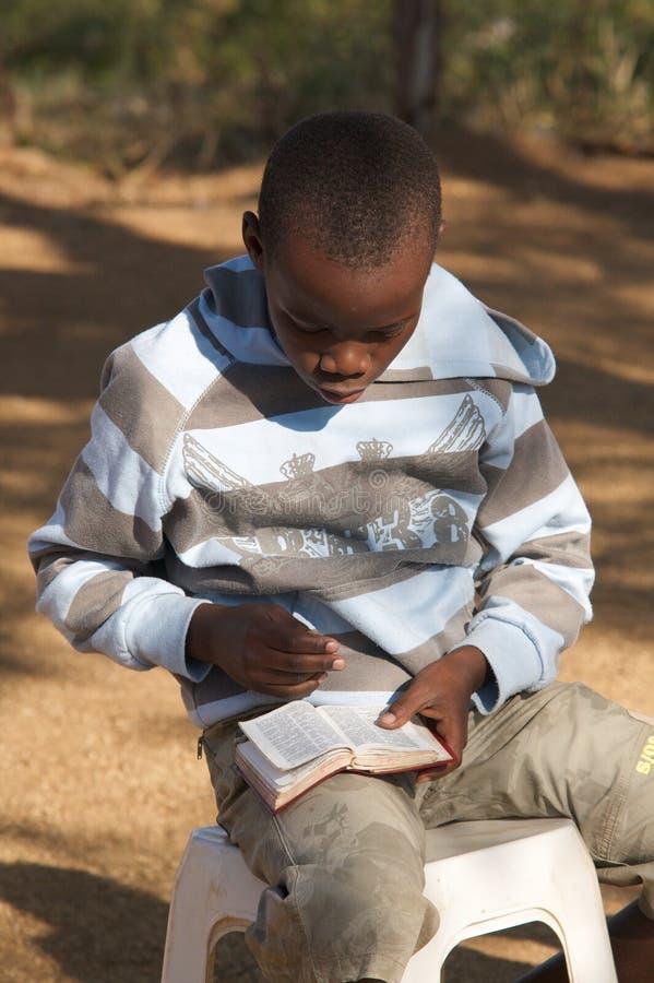 Afrikanischer Junge, der seine Bibel liest lizenzfreies stockbild