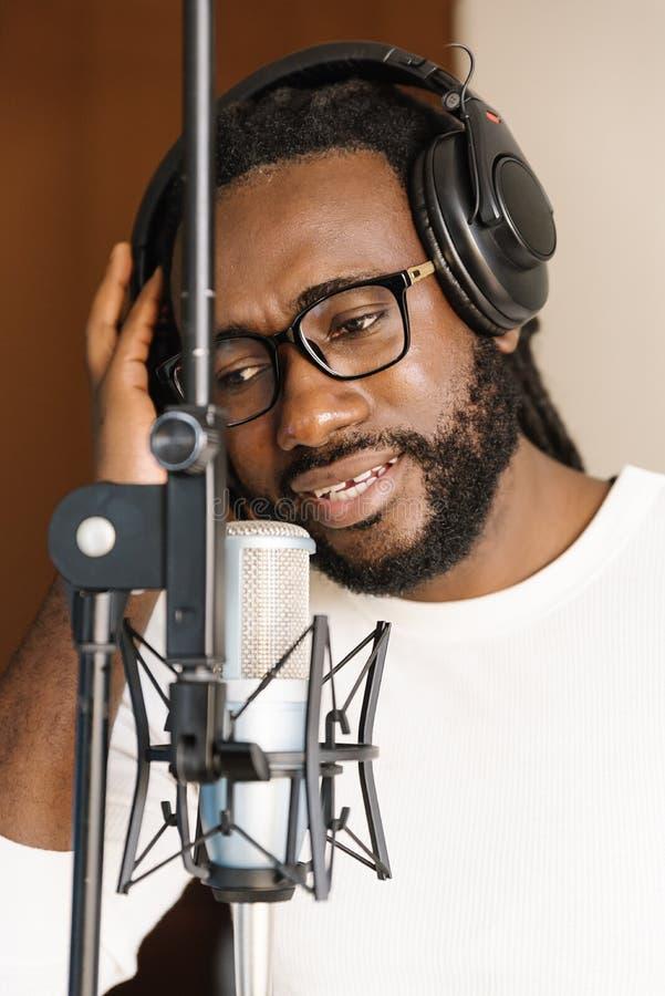 Afrikanischer junger Mann, der auf musikalischem Studio singt stockbilder