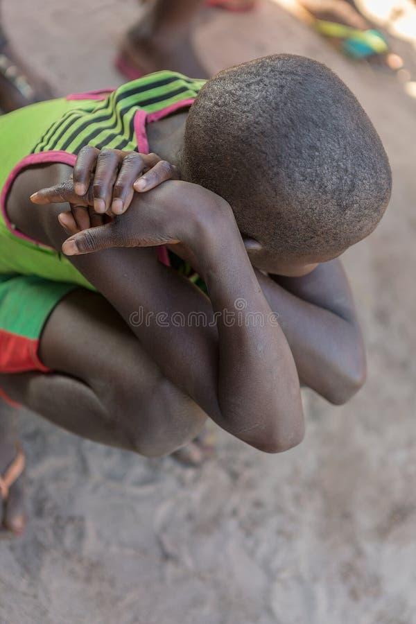 Afrikanischer ländlicher Junge, geduckt lizenzfreie stockfotos