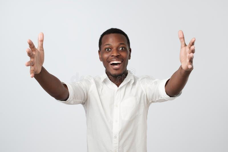 Afrikanischer Mann Cheerfull im weißen Hemd, Hände in Richtung zur Kamera ziehend und wünschen streicheln lizenzfreies stockbild