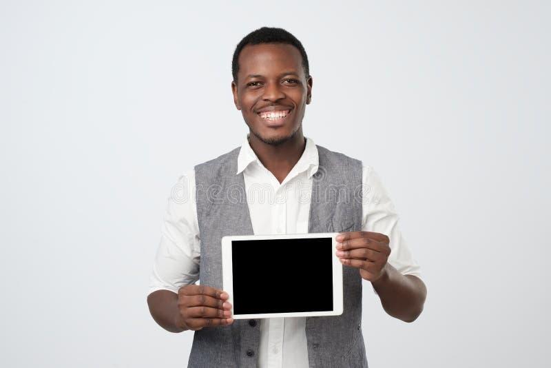 Afrikanischer Mann, der leeren Bildschirm der modernen Tablette lächelt und zeigt lizenzfreies stockbild
