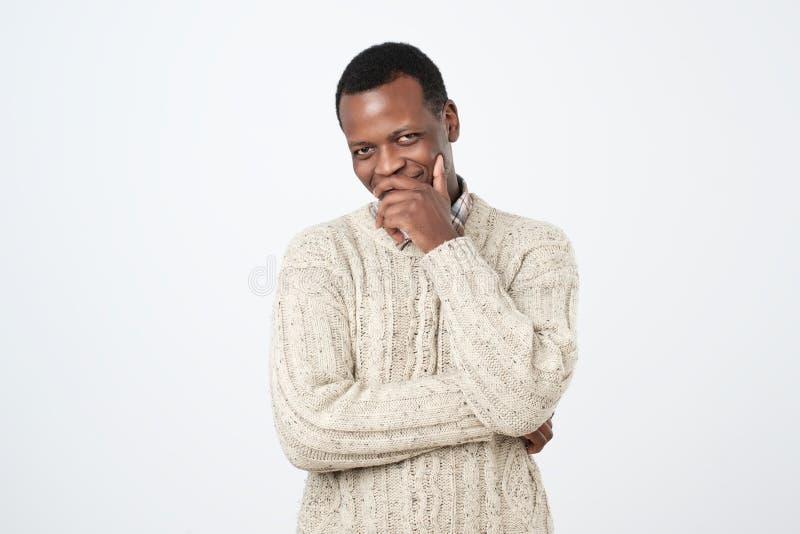 afrikanischer Mann, der seinen Mund mit lacht und bedeckt, weißen Hintergrund zu überreichen Versuchen, ein Lachen zu halten, um  lizenzfreies stockbild