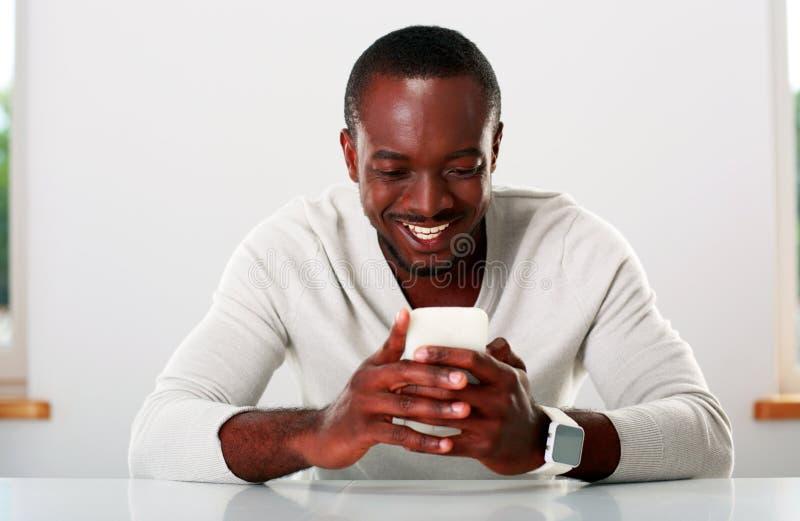 Afrikanischer Mann, der Smartphone verwendet lizenzfreie stockbilder