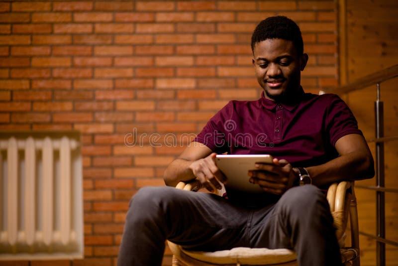 Afrikanischer Mann, der Tablette für Videogespräch bei der Entspannung auf Lehnsessel verwendet lizenzfreies stockfoto