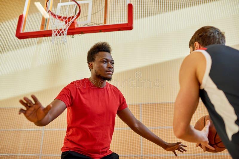Afrikanischer Mann, der Verteidigung im Basketball spielt lizenzfreies stockbild