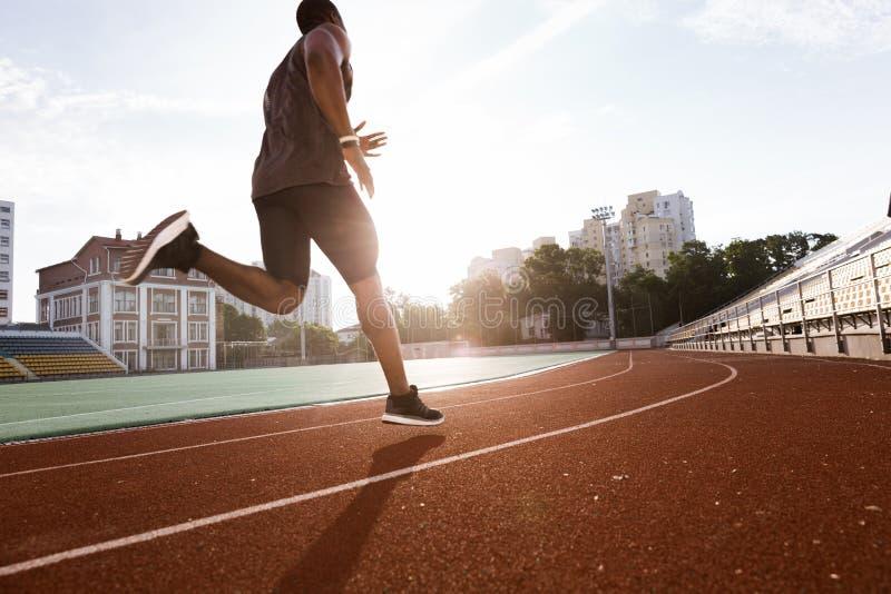Afrikanischer Mann des Athleten, der auf Rennbahn läuft stockbilder