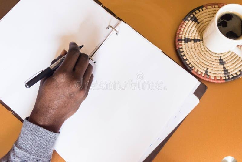 Afrikanischer Mannbehälter in der Hand, zum auf leeres Weißbuch zu schreiben lizenzfreie stockbilder