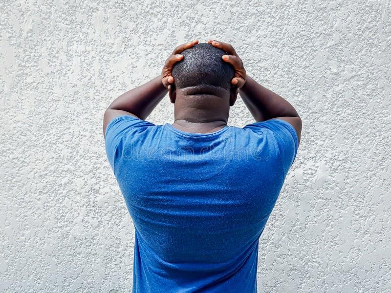Afrikanischer Mannholdingkopf in seinem Hand-, besorgtes, erschrockenen oder unglücklichen Ausdruck, hintere Ansicht lizenzfreie stockfotografie