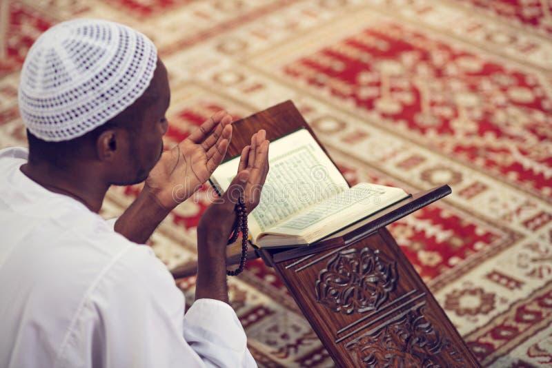 Afrikanischer moslemischer Mann, der dem Gott traditionelles Gebet beim Tragen von Dishdasha macht lizenzfreies stockbild