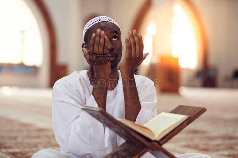 Afrikanischer moslemischer Mann, der dem Gott traditionelles Gebet beim Tragen von Dishdasha macht stockbild