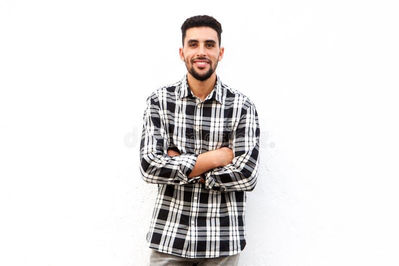 Afrikanischer Nordmann, der gegen weißen Hintergrund mit den Armen gekreuzt lächelt lizenzfreies stockfoto