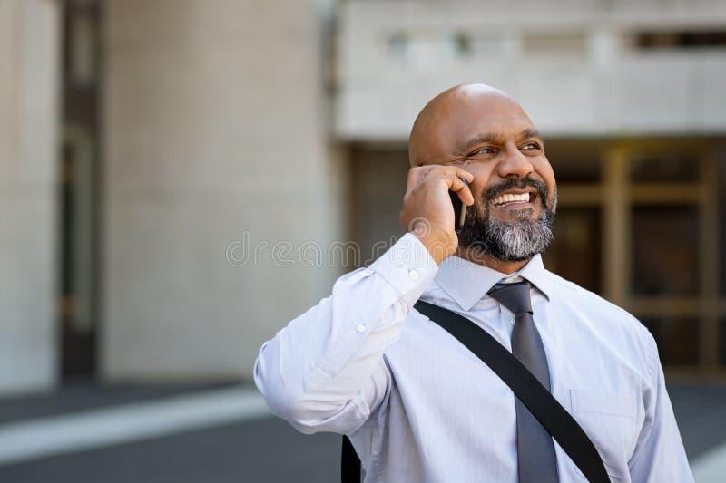 Afrikanischer reifer Geschäftsmann, der am Telefon im Freien spricht stockfotografie