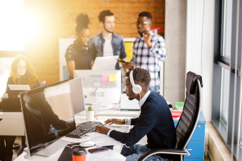 Afrikanischer schöner Programmierer mit den Kopfhörern, die mit Computer arbeiten lizenzfreie stockbilder